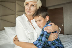 Mother and son sitting on a bed and cuddling Stock Photography