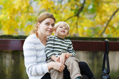 Mother and son sitting on bench in autumn park Stock Images