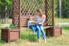 Mother with son sitting on a bench in park and reading book Royalty Free Stock Images