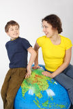Mother and son sitting on big inflatable globe Stock Photo