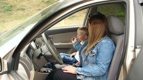 Mother and son are sitting in the car in the front seat, the child eats candy. Mother and son are sitting in the car in the front seat, the child eats candy on stock video footage