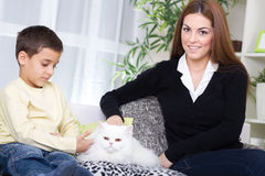 Mother and son sitting on the couch and caressing a white Persia. Mother son and white Persian cat Royalty Free Stock Images