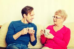 Mother and son sitting on couch and drinking tea or coffee.  royalty free stock images