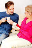Mother and son sitting on couch and drinking tea or coffee Stock Photography