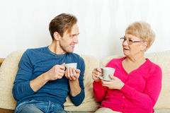 Mother and son sitting on couch and drinking tea or coffee Stock Photos
