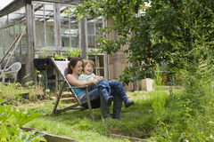 Mother And Son Sitting On Deck Chair In Allotment Stock Photos