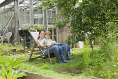 Mother And Son Sitting On Deck Chair In Allotment Royalty Free Stock Photography