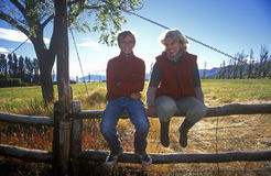 Mother and son sitting on a fence in El Calafate, Patagonia, Argentina Stock Images