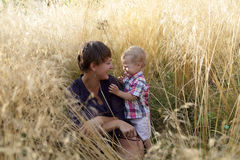 Mother and son sitting in field of grass Royalty Free Stock Image