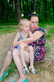 Mother and son sitting in the green forest Stock Photography
