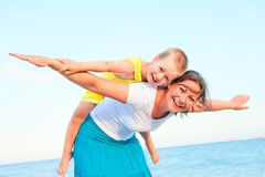 Mother and son sitting on her back, happy playing Royalty Free Stock Images