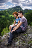 Mother and son sitting on a mountain top Stock Images