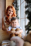 Mother and son sitting near the window in the room with the Christmas decorations. Stock Images