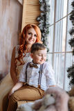 Mother and son sitting near the window in the room with the Christmas decorations. Royalty Free Stock Images