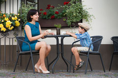 Mother and son sitting in outdoor cafe. This image has attached release Stock Images