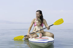 Mother and son sitting on a paddle board Stock Photos