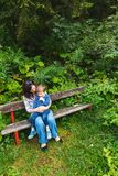 Mother and son sitting on park bench stock image