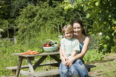 Mother And Son Sitting On Picnic Table In Allotment Royalty Free Stock Images