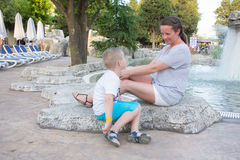 Mother and son sitting on a rock Stock Photos