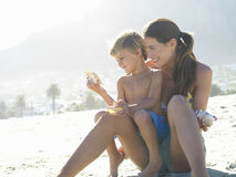Mother and son (4-6) sitting on sandy beach, holding sea shells, boy in woman's lap Stock Photos