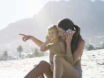 Mother and son (4-6) sitting on sandy beach, holding sea shells, boy in woman's lap, pointing Royalty Free Stock Images