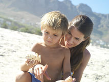 Mother and son (4-6) sitting on sandy beach, holding sea shells, boy in woman's lap (tilt) Stock Photography