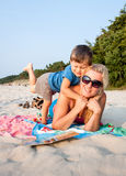 Mother and son sitting on sandy beach reading a bo Stock Photo