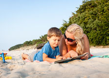 Mother and son sitting on sandy beach reading book Stock Photo