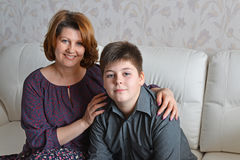 Mother and son sitting on a sofa in room Stock Photos