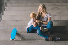Mother with son sitting on a stairs. With skateboard Stock Photography
