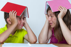 Mother and son sitting at the table with books. Funny portrait of smiling mother and son sitting at the table with books on heads, trying to do homework lessons Royalty Free Stock Image