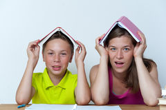Mother and son sitting at the table with books. Funny portrait of smiling mother and son sitting at the table with books on heads, trying to do homework lessons Stock Images