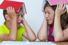Mother and son sitting at the table with books. Funny portrait of smiling mother and son sitting at the table with books on heads, trying to do homework lessons Stock Photography