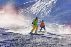 Mother and son ski down the mountain Royalty Free Stock Photography
