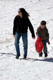 Mother and son sledding. A mother and son walking back up a snow covered hill with a sled Stock Photography