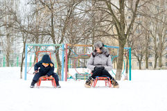 Mother and son sledding in winter Stock Image