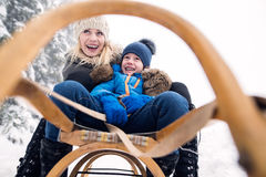 Mother with son on sledge. Foggy white winter nature. Royalty Free Stock Images