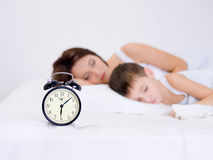 Mother and son sleeping. Beautiful young mother and her preschool son sleeping with alarm clock royalty free stock images
