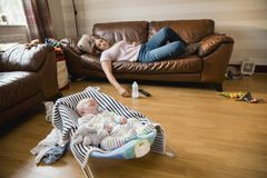 Mother and Son Sleeping at Home. Exhausted mother having a nap on the sofa while her newborn child has a sleep royalty free stock images
