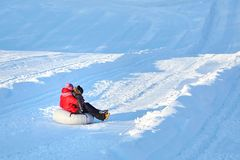 Mother and son sliding on snow tubing down the hill stock photos