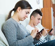 Mother and son with smartphones at home Stock Photos