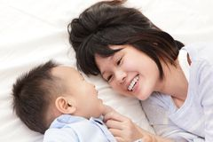 Mother and son smile and look each other. And lying on white bed in the bedroom at home, asian family Royalty Free Stock Images