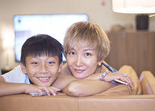 Mother & son smiling at camera on couch Royalty Free Stock Photography
