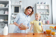 Mother and son are smiling while having a breakfast in kitchen. Mom is pouring milk and corn flakes into glass. Mother and son are smiling while having a Stock Image