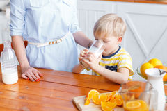 Mother and son are smiling while having a breakfast in kitchen. Mom is pouring milk into glass. Morning Stock Image
