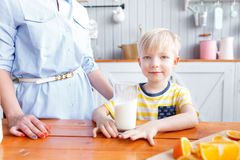 Mother and son are smiling while having a breakfast in kitchen. Mom is pouring milk into glass. Morning Royalty Free Stock Photos