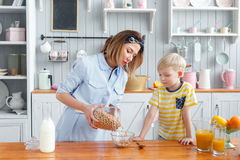 Mother and son are smiling while having a breakfast in kitchen. Mom is pouring milk and corn flakes into glass. Mother and son are smiling while having a Royalty Free Stock Images