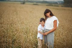 Mother with son smiling holding hands and embracing in a field in summer. The concept of maternal love and tenderness, the royalty free stock photo