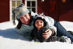 Mother and son on snow. Portrait of a smiling mother and her infant son laying on snow in front of a cottage on a sunny winter day Stock Photography