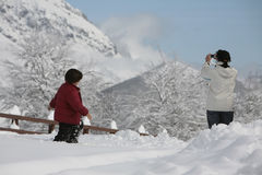 Mother and son in the snow. Taking a photo Royalty Free Stock Images